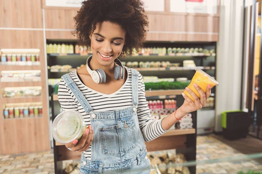 girl is standing in organic shop and choosing healthy food for weight loss