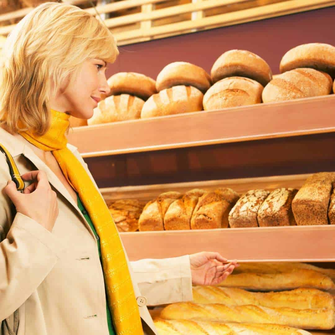 A woman buying bread in the shop
