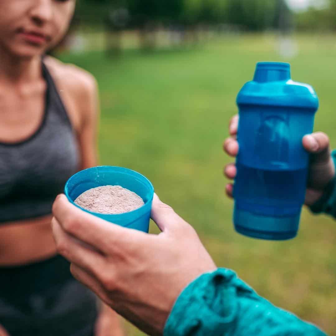 A woman taking protein after running