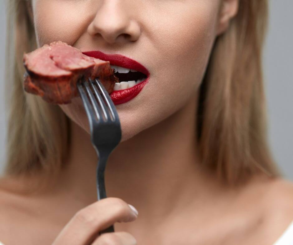 a woman eating a piece of meat